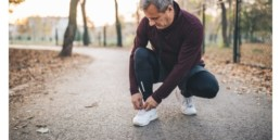 Senior man with the right footwear for foot pain, taking a pause from jogging to tie his shoelace