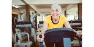 Mature woman with flat feet exercising on a treadmill in a gym