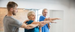 Seniors doing nerve flossing exercises with a physical therapist helping woman while doing arm exercise.