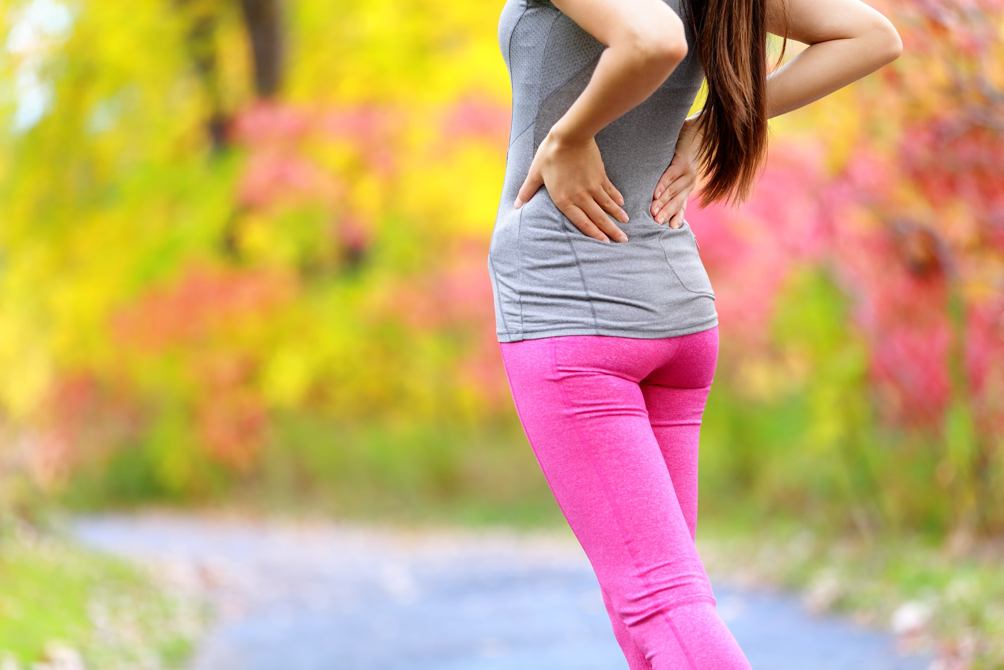 Lower Back pain. Running woman with back injury in sportswear rubbing touching lower back muscles standing on road outside in forest in fall.