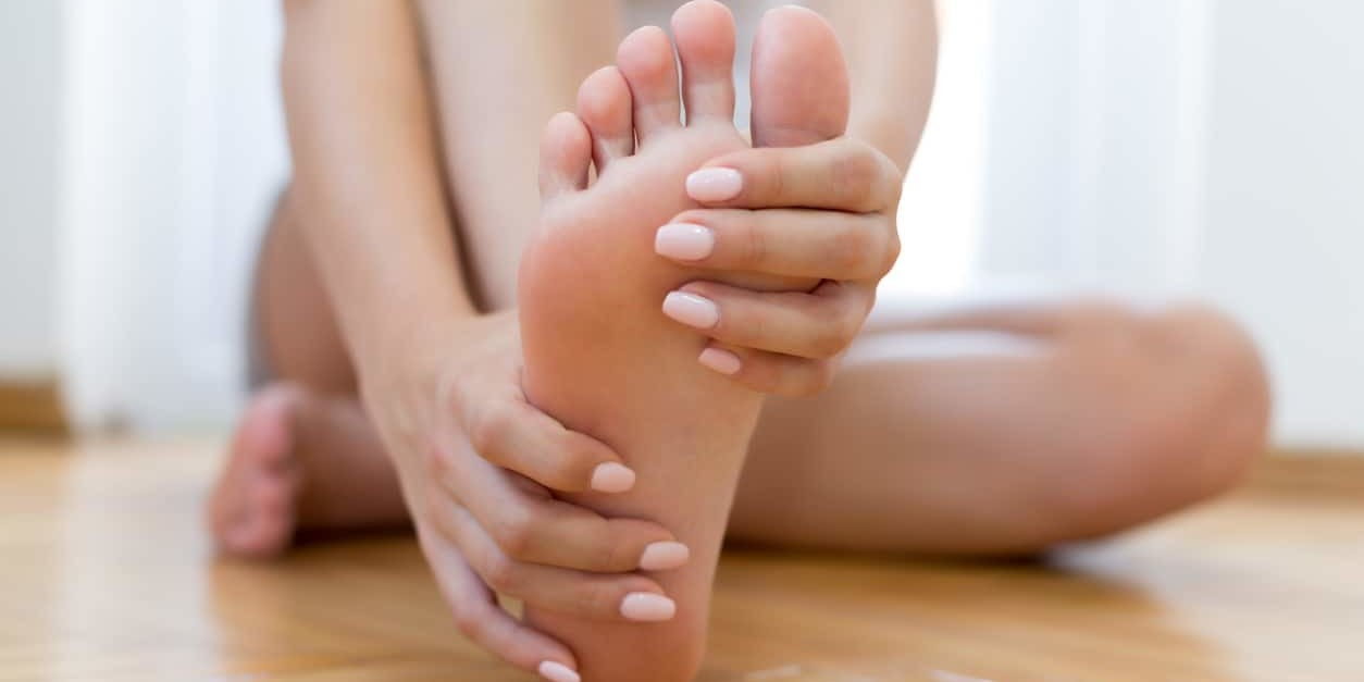 Closeup young woman feeling pain in aching feet