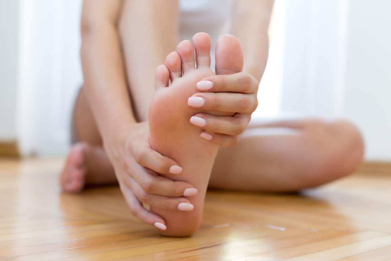 Closeup young woman feeling pain in aching feet