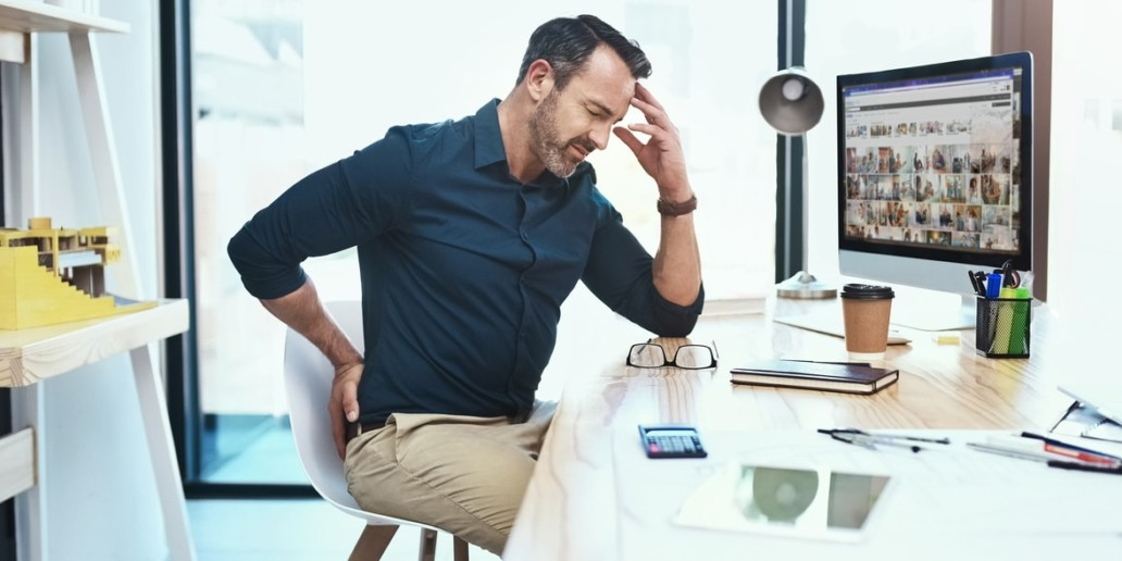 Shot of a mature businessman experiencing back pain while working at his desk. How to prevent lower back injury.