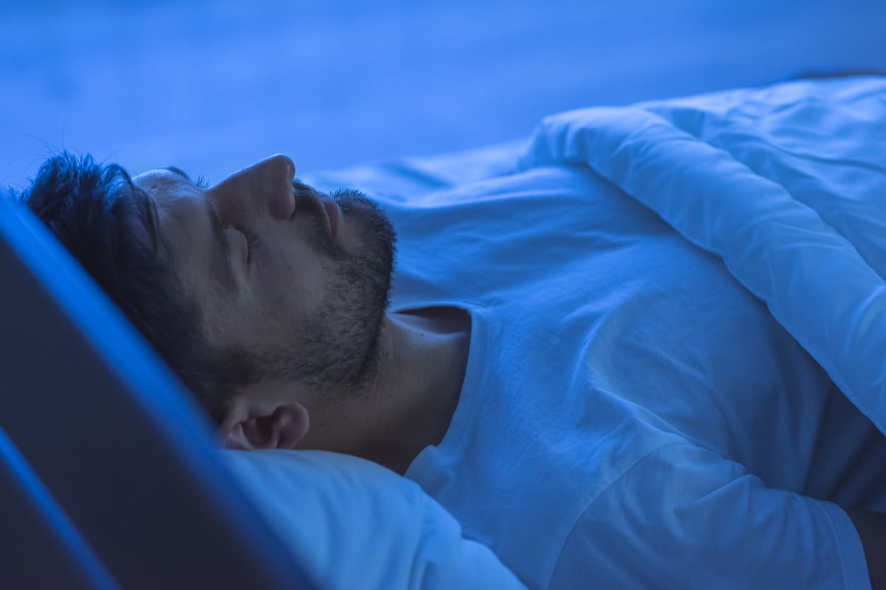 A man sleeping in bed at night finding relief from back pain with the right pillow