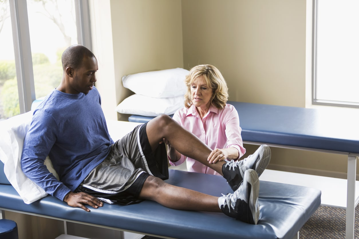 A female physical therapist examining a young African American man for knee injuries on a treatment table. He is sitting on the table with his legs stretched out in front of him. The physical therapist, a senior woman, is examining his knee. They are both looking at his bent knee with serious expressions on their faces.