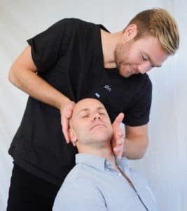Physical therapist adjusting a patient's neck