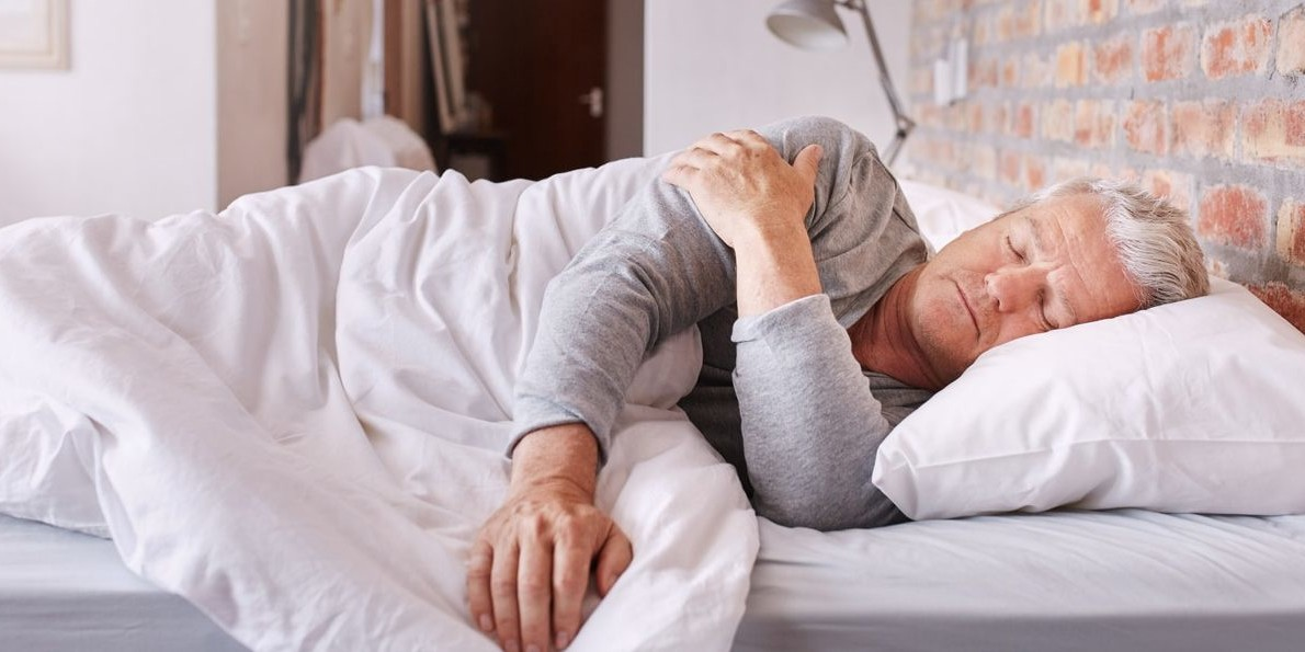Shot of a senior man sleeping in bed holding his shoulder because of shoulder pain at night