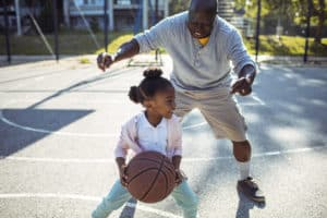 grandfather playing basketball with granddaughter