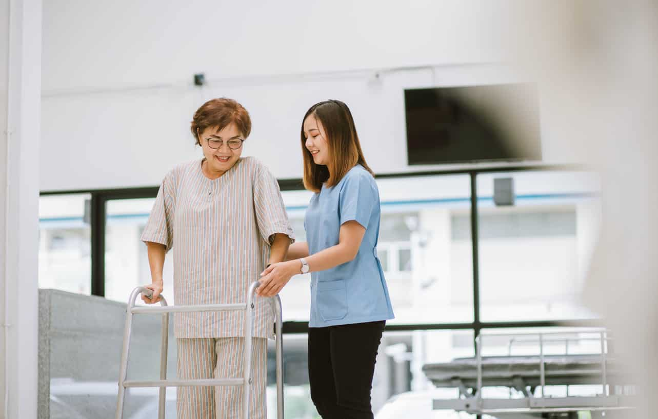physical therapist helping patient with walker