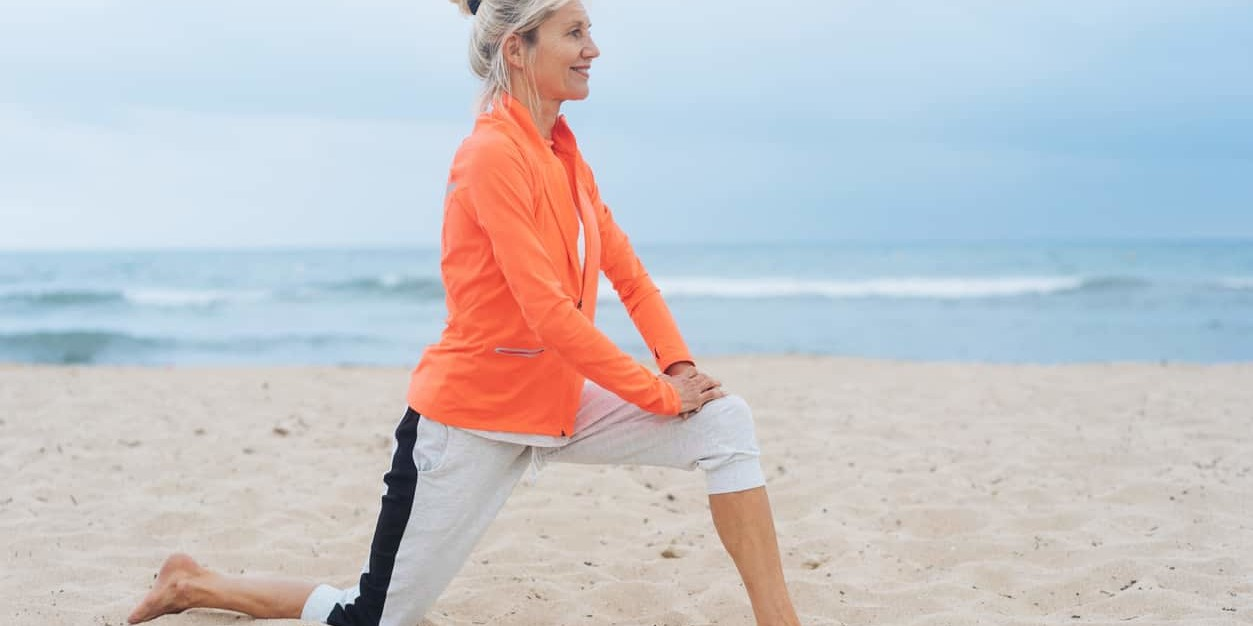 stretching knee on beach