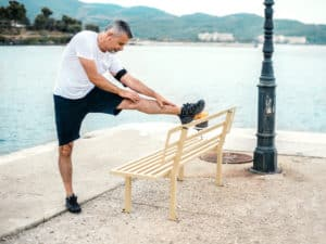 Person stretching leg   knee pain Cawley Physical Therapy