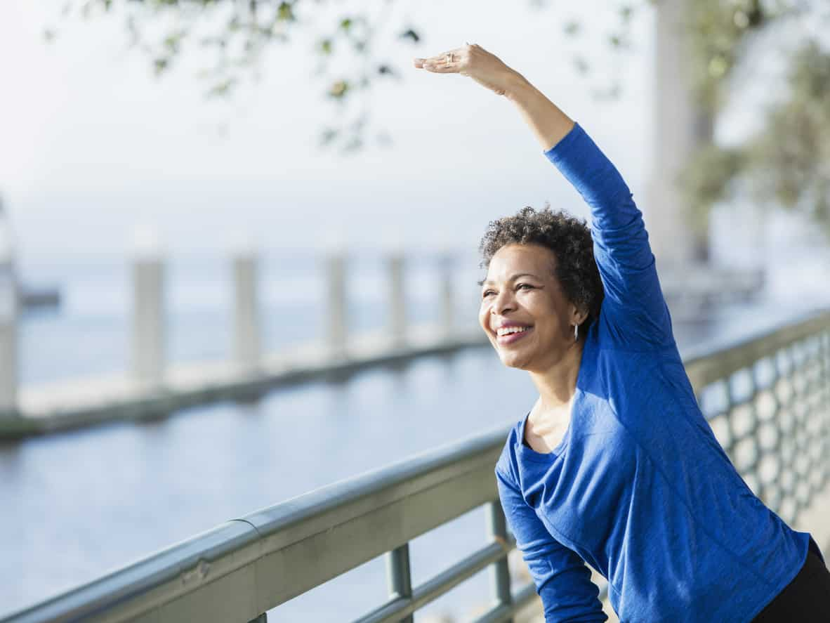 Person stretching by water | posture Cawley Physical Therapy and Rehab