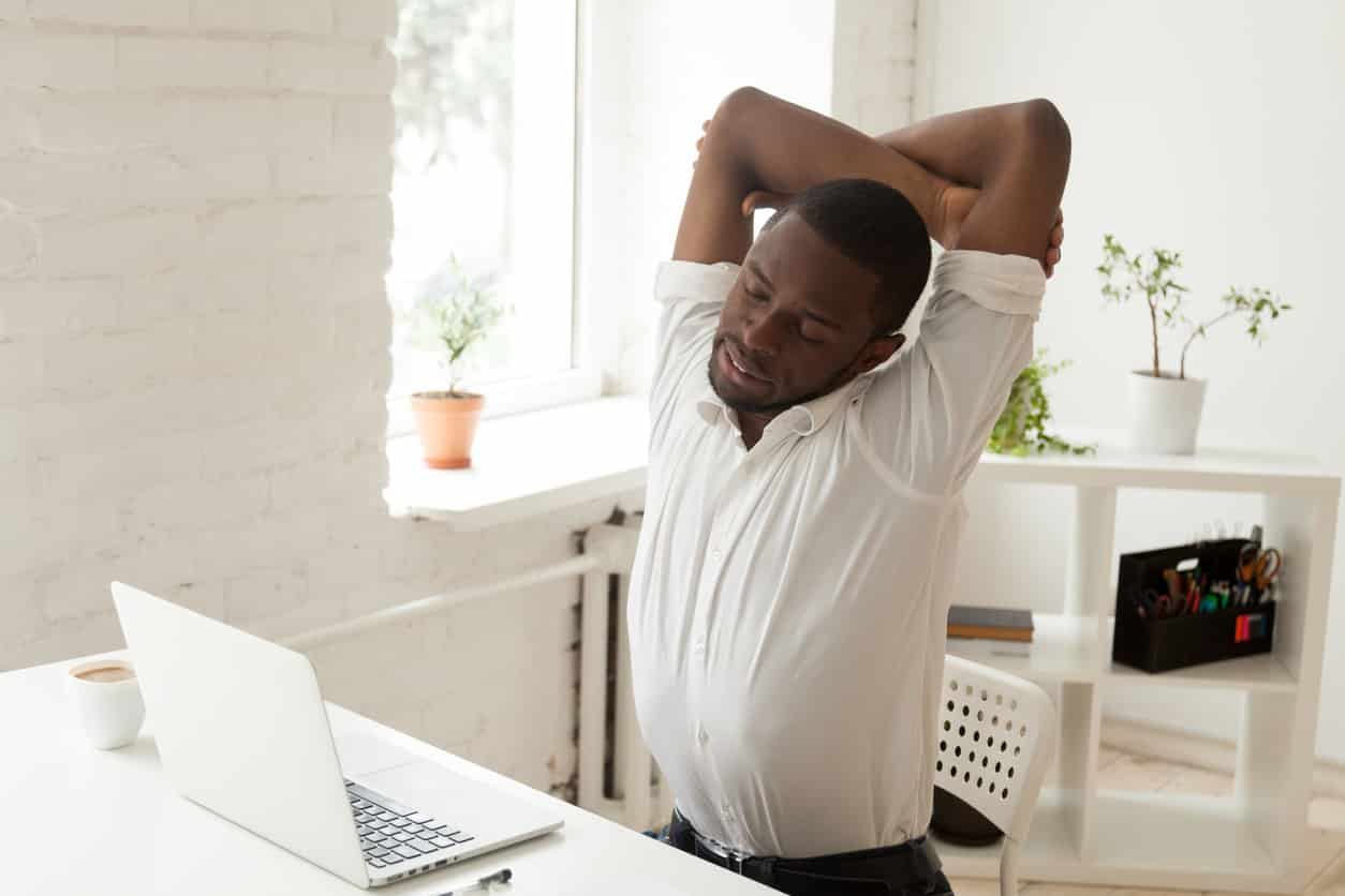 Person stretching at their desk | Cawley Physical Therapy and Rehab