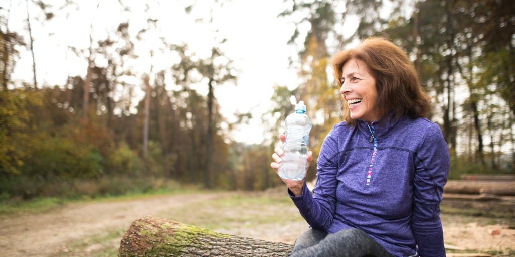 a woman drinking water to stay hydrated