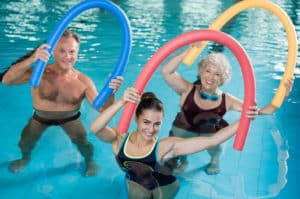 physical therapist with two seniors in an aquatic therapy class
