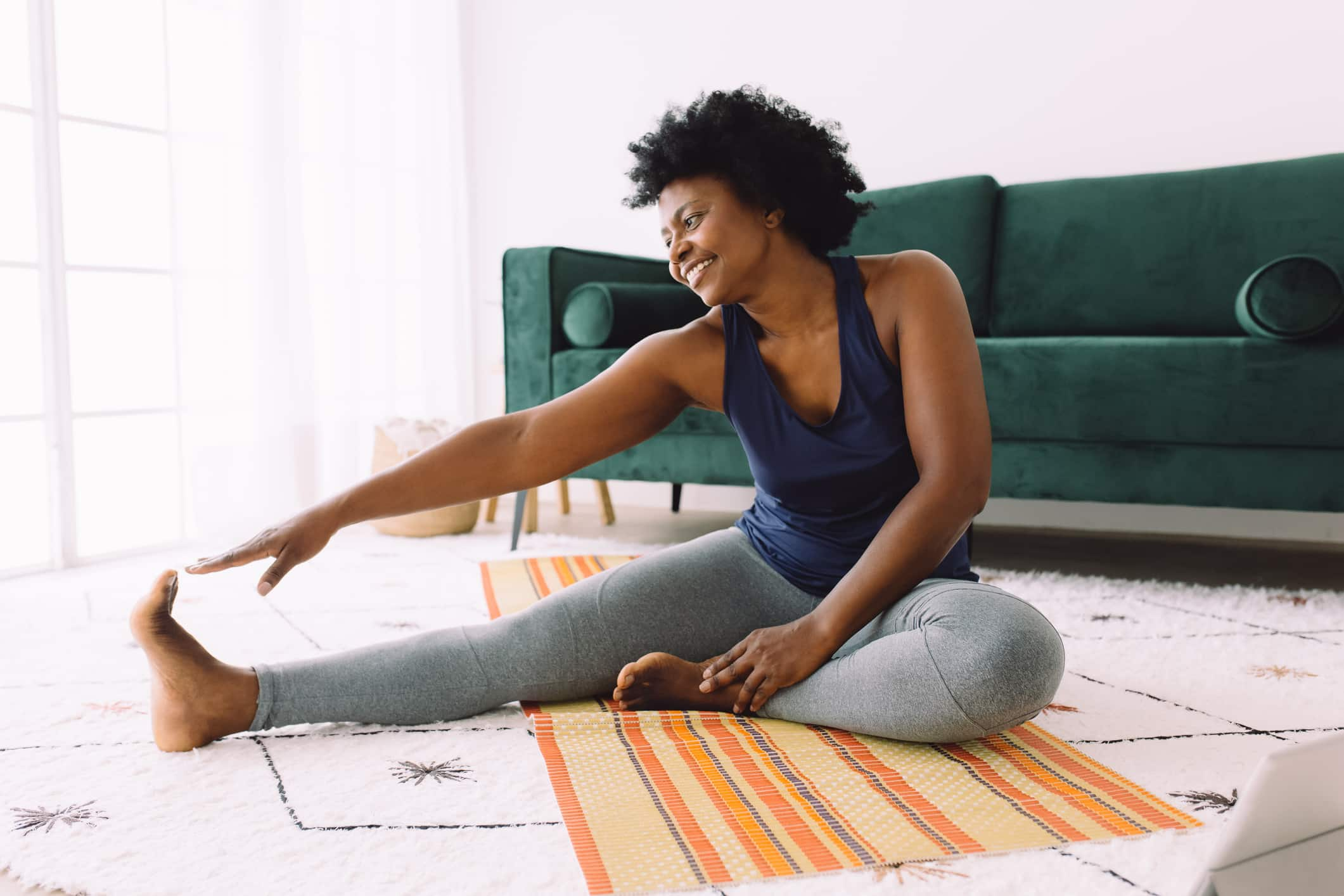 African-American woman doing a leg stretch on a yoga mat at home