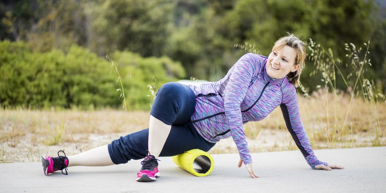 young woman foam rolling her hips before exercising outdoors