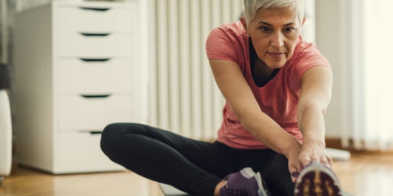 woman doing a hamstring stretch at home to improve balance